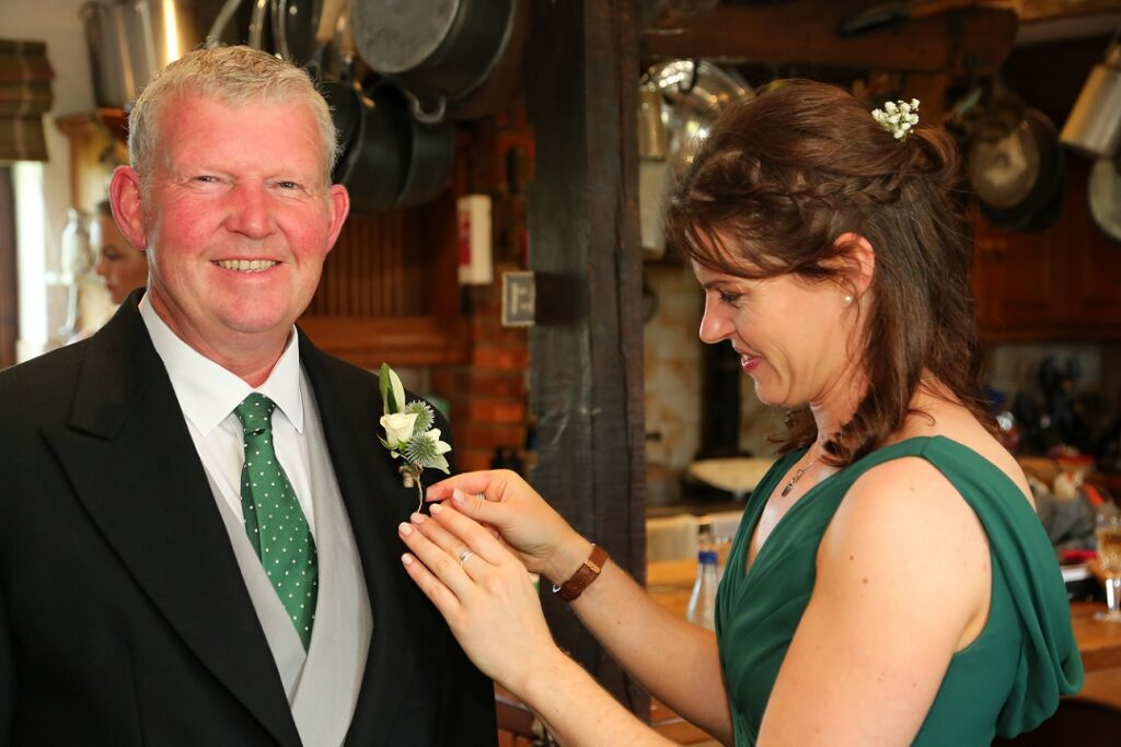Bridesmaid pinning buttonhole on Father of the Brides Morning Suit.