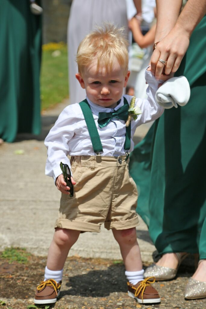 Cute pageboy wearing green braces and shorts.