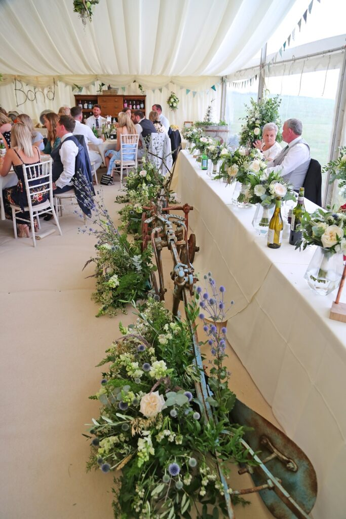 Top table wedding flower display in marquee at the farm.