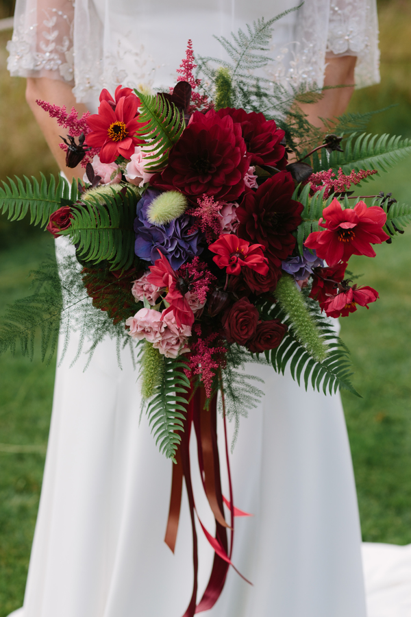 Large textured bridal bouquet in reds and purples. Model wearing Madi Lane Bridal Gown.