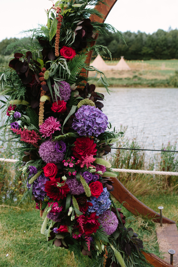 Close up of floral arch created by Signature Flowers Bucks and Oxon, in purples and reds.