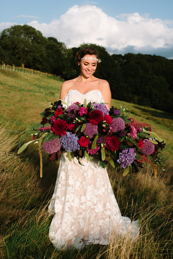 Large wedding floral display in reds and purples. Model wearing Madi Lane Bridal Gown.