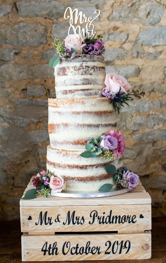 Rustic naked wedding cake with pretty fresh flowers.