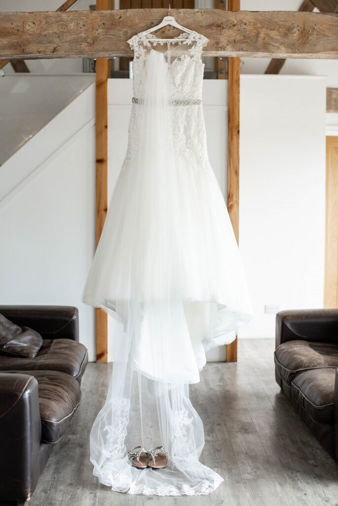 Maggie Sottero wedding dress and veil hanging in dressing room.
