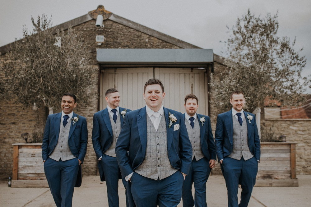 Groom and his groomsmen in navy suits.