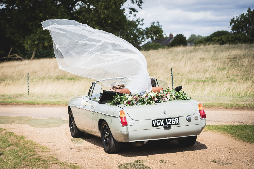 Wedding Car driving off with Bride's veil blowing in the wind