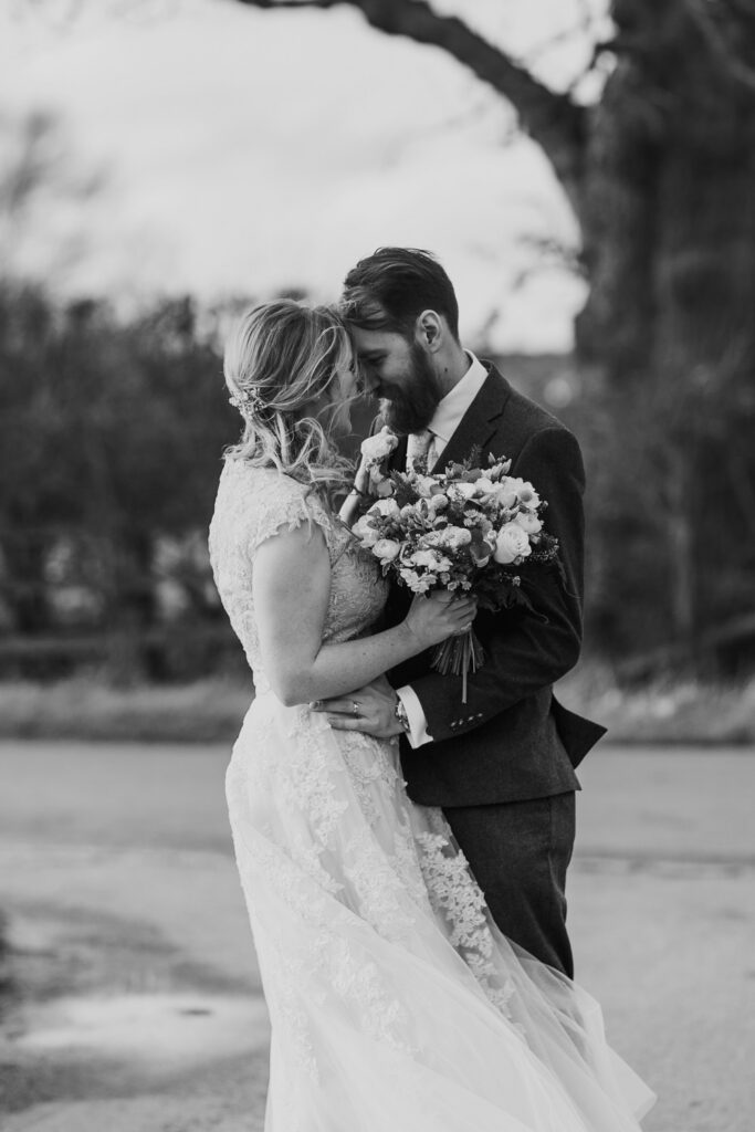 Black and white image of bride and groom in embrace