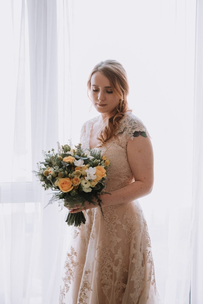 Bride holding her yellow and white bridal bouquet