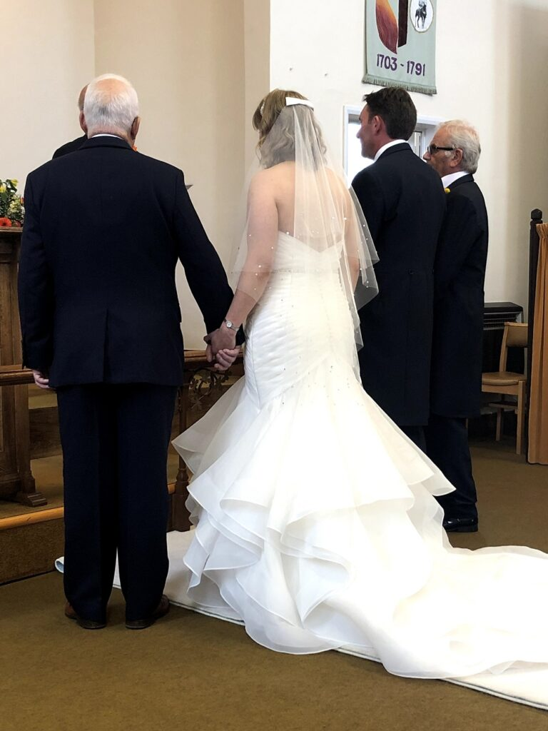 Bride holds her Father's hand at the Altar.
