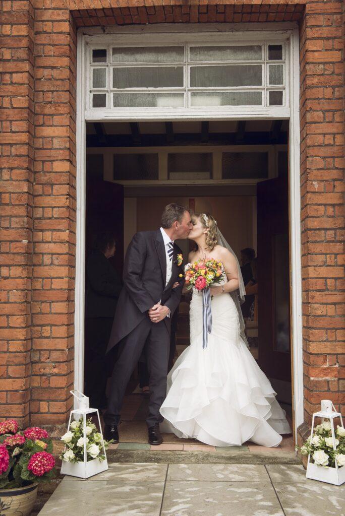 Bride and Groom kissing in doorway.