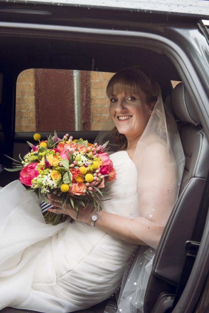 Bride sitting in the wedding car.