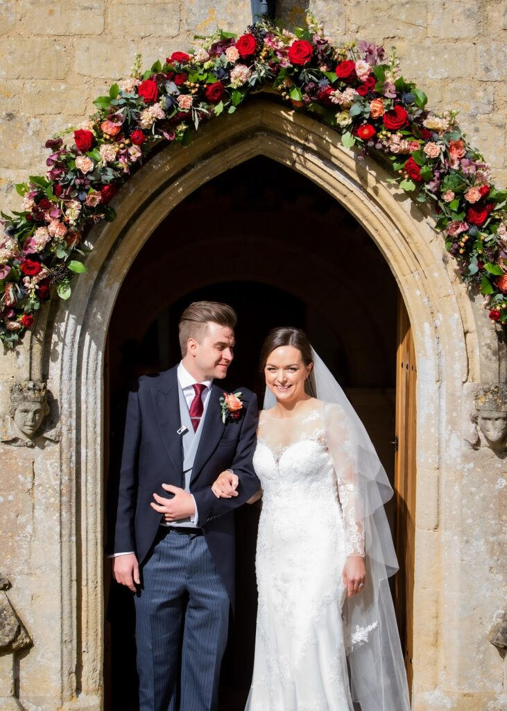 Bride and Groom under floral arch at church