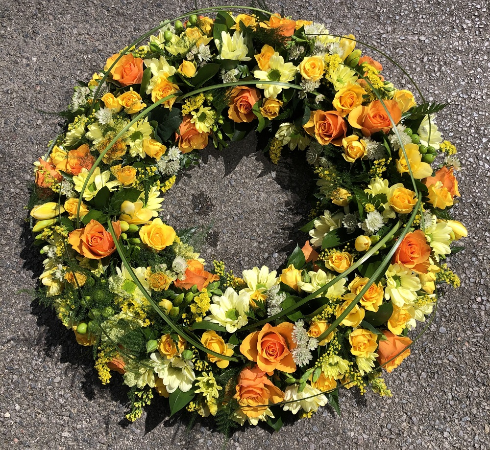 Pretty yellow and white funeral wreath